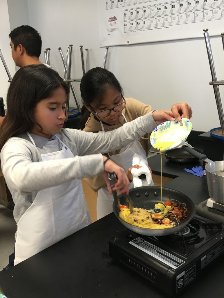 Cook Club students stir the egg